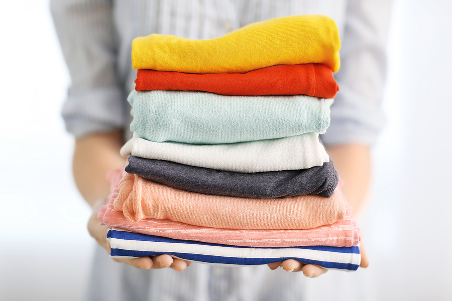 bigstock-Woman-holding-stack-of-clothes-161462567